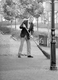 Gerrit van Essen, op hoge leeftijd nog bezig met zijn zo herkenbare klus: bladvegen rond de kerk.(de foto is uit 2000)