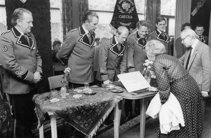 Receptie t.g.v. het 90-jarig jubileum van Caecilia op 2 oktober 1982. Het toenmalig burgemeestersechtpaar, de heer en mevrouw Heij, met achter de tafel v.l.n.r. de heren H. Schippers, B. van de Wetering, G. van de Haar, W. van Oostrom, J. Cozijnsen.