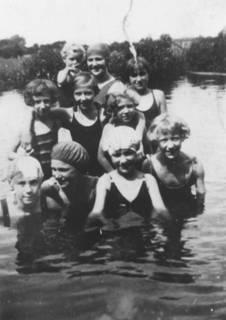 Groepje zwemmers in zwembad 't Schut. Op de foto bovenaan: Leentje Minnen met Miep op de arm. Daaronder v.l.n.r.: Cor Wolswinkel, Mary Blanken, Clara Goldstein en Sjaan Minnen. Onderste rij v.l.n.r.: Janny Berendse, Bertha Minnen, Adri Berendse en Jenny van der Ham.