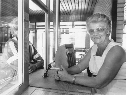 """Mevrouw """"Moe"""" Huijbers achter de kassa, 1982"""