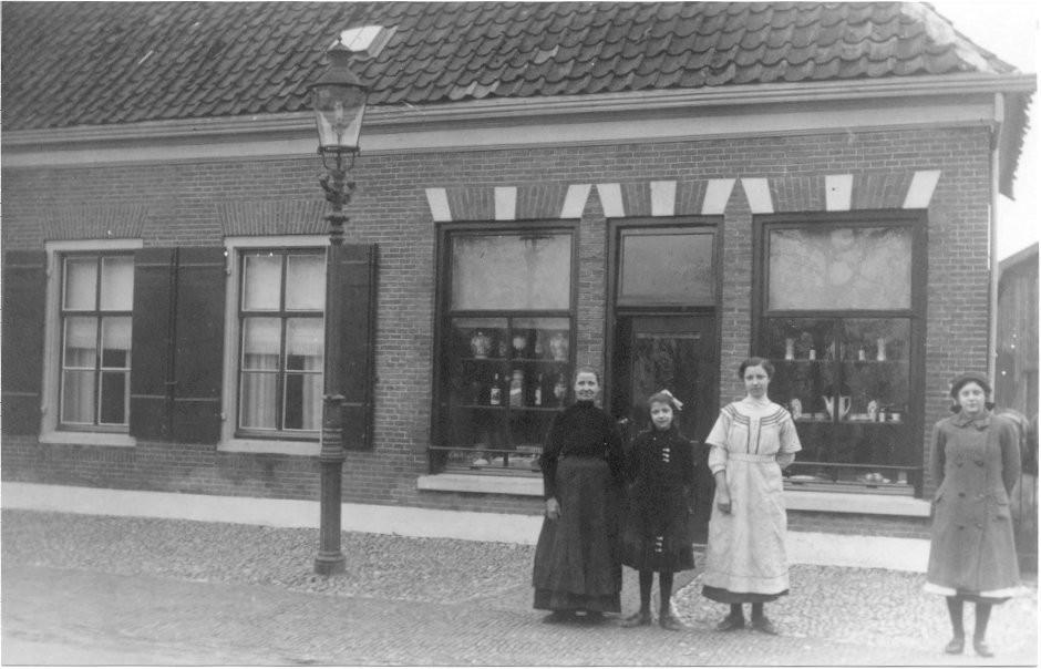 Vlnr: Mevrouw Kuiper, dochters Carolien en Dina, Riek Vlastuin. De dames staan voor de winkel van Bart Kuiper aan de Dorpsstraat. ± 1920